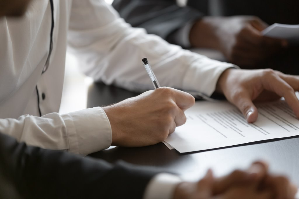 close-up-young-male-manager-hands-signing-contract-picture-id1191132035